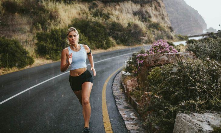woman running on side of road