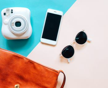 Flat lay of brown leather hand bag open out with accessories, instant camera and smartphone on colorful background