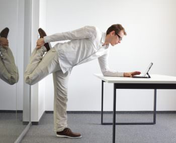 A man stretching one of his legs at is desk